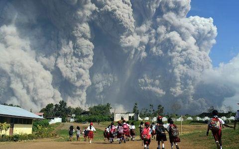 School children walk as Mount Sinabung erupts in Karo, North Sumatra, Indonesia, Monday, Feb. 19, 2018 - Credit: Sarianto/AP